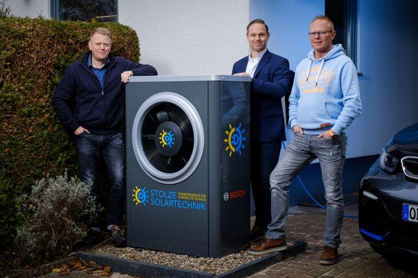 Drei Männer stehen neben einer Luft/Wasser-Wärmepumpe.