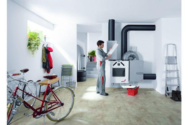 Ein Mann steht neben einem System zur Wohnraumlüftung.