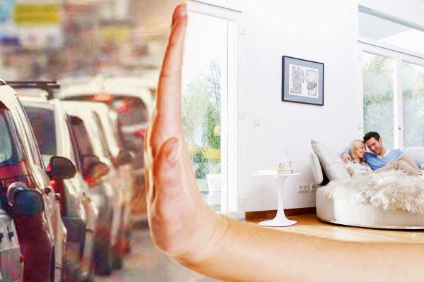Das Bild zeigt links eine stark befahrene Verkehrsstraße und rechts ein Paar, das bequem auf einem Sofo in der Wohnung liegt. In der Bildmitte symbolisiert eine Hand, dass der Lärm draußen bleibt.