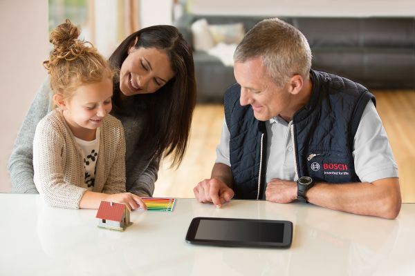 Eine Frau, ein Mann und ein Kind sitzen vor einem Tablet.