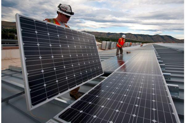 Zwei Handwerker installieren Solarmodule auf einem Dach.