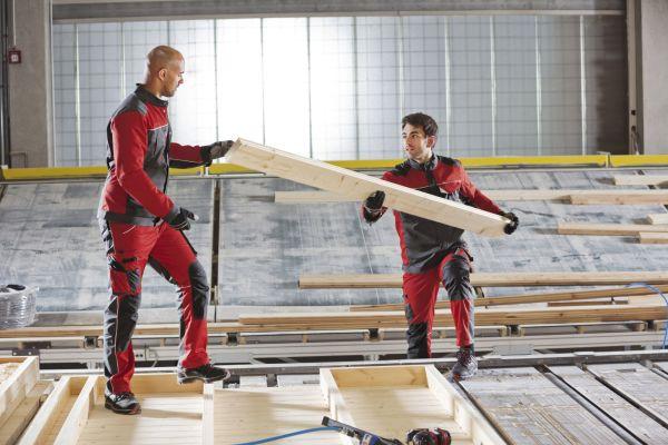 """Das Bild zeigt zwei Handwerker in der rot-grauen Arbeitskleidung """"MEWA Dynamic Construct"""" von MEWA auf einer Baustelle. Bei Handwerkerkleidung sind praktische Details wie Taschen und Schlaufen, für Hammer, Zollstock und Kleinteile wichtig."""