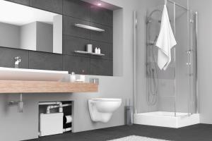 """Das Bild zeigt ein Badezimmer. Unter dem Waschtisch befindet sich ein Ausschnitt, in dem die Hebeanlage """"Sanipack"""" von SFA Sanibroy zu sehen ist, die das Abwasser von WC, Dusche, Waschtisch und Bidet beziehungsweise Urinal entsorgt."""