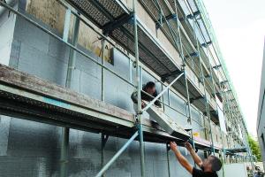 Das Bild zeigt einen Handwerker, der seinem Kollegen auf dem Gerüst eine Styropor-Platte anreicht.