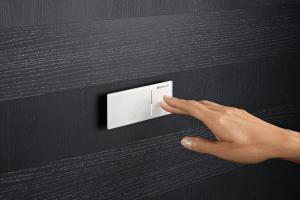 Das Bild zeigt eine kleine Geberit-Betätigungsplatte aus weißem Glas, die frei an einer aus dunklem Holz verkleideten Wand platziert wurde und somit maximale Flexibilität bietet.