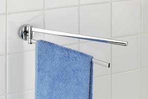 """Das Bild zeigt den verchromten Handtuchhalter aus der """"VACUUM-LOC""""-Serie """"Capri"""" von Wenko. Er ist an einer weiß gefliesten Wand angebracht und trägt ein blaues Handtuch."""