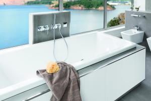 """Das Bild zeigt eine Armaturenstele für Wannen aus der """"MULTISTAR VISION""""-Produktserie von Schedel, die sich für den freistehenden Einbau in Verbindung mit einem Wannenträger eignet. Angebracht ist die Stele nebst verchromten Armaturen an einer freistehenden, weißen Wanne, die sich vor drei großen Panoramafenstern befindet."""
