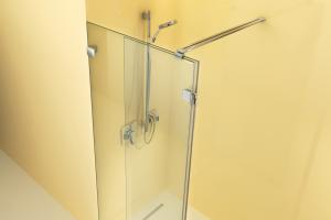 """Im Bild ist die gläserne Duschenwand """"ARTWEGER 360"""" in der türlosen """"Walk In Vario""""-Ausführung von Artweger vor einer gelben Wand zu sehen."""