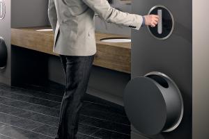 Der runde Papierspender von Vola fasst bis zu 100 Handtücher. Er wird in die Wand des Bades eingebaut.