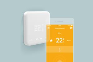 Das Smarte Thermostat zur Heizungsregelung und die App auf einem Smartphone.