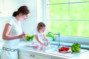 Eine Frau und ein Mädchen waschen an einem Küchen-Wasserhahn Gemüse.
