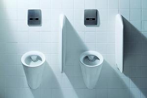 Das Bild zeigt zwei Urinale aus weißer Keramik von Duravit, die durch Trennwände voneneinander getrennt sind. Sie sind an einer weiß gefliesten Wand angebracht. Über den Urinalen befinden sich Betätigungsplatten aus Edelstahl.