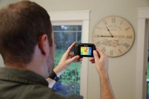 Die FLIR C2 lokalisiert mittels Thermografie eine warme Rohrleitung hinter einer Wanduhr.