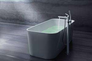 """Das Bild zeigt die weiße Standarmatur aus der Serie """"Balance White"""" von Kludi, die auf einem hölzernen Boden vor einer weißen Badewanne platziert wurde."""
