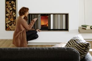 """Das Wärmeschutzschild """"heatStop"""" vor einem Kaminofen."""
