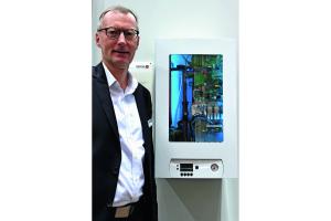 Der Geschäftsführer von Brötje mit der Luft/Wasser-Wärmepumpe SensoTherm BLW Split auf der ISH 2017.