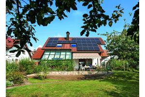 Einfamilienhaus mit Photovoltaik-Anlage auf dem Dach.