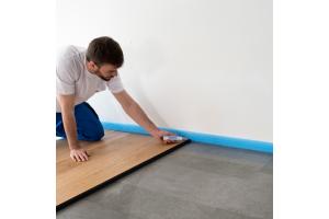 Ein Installateur bringt Randdämmstreifen bei einer Fußbodenheizung an.