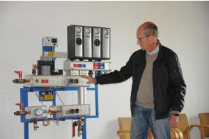 Der Vorstand der Energiegenossenschaft WeilerWärme eG Klaus Gall zeigt, wie die Übergabestationen der Nahwärmeversorgung funktionieren.