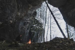 Ein Mann sitzt in einem verschneiten Wald vor einem Lagerfeuer.