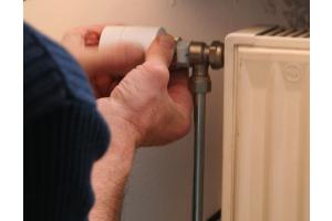 Ein Monteur bringt ein neues Thermostat an einem Heizkörper an.