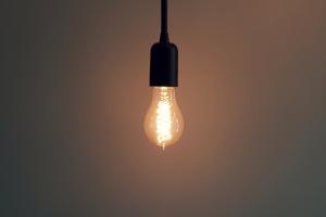 Eine brennende Glühbirne in einem dunklen Raum.