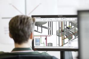 """Ein Mann betrachtet die Planungssoftware """"Viptool Engineering"""" von Viega auf einem Computerbildschirm."""