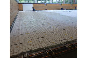 Fußbodenheizungsrohre auf dem Boden einer Sporthalle.