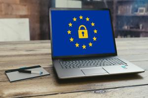 Ein aufgeklappter Laptop mit dem Bild einer EU-Flagge und eines Schlosses.