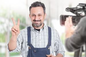 """Ein Handwerker macht ein """"Peace""""-Zeichen vor einer Kamera."""
