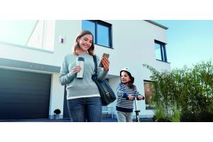 Eine Frau schaut vor einem Haus auf ihr Smartphone.