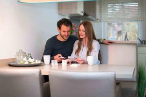 Ein Mann und eine Frau sitzen an einem Küchentisch.