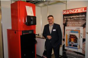 Geschäftsführer Tim Künzel von der Künzel Heiztechnik GmbH zeigt auf der IFH/INTherm 2018 seinen Kombi-Heizkessel für Holzvergaser und Öl/Gas.
