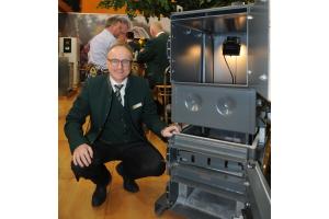 """KWB-Geschäftsführer Dipl.-Ing. Dr. Helmut Matschnig mit dem Pellet-Brennwertkessel """"KWB Easyfire CC 4"""" auf der IFH/Intherm 2018."""
