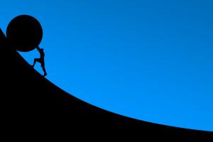 Die Silhouette eines Mannes rollt vor einem blauen Hintergrund einen Stein einen Berg hoch.