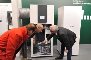 Drei Männer betrachten die Luft/Wasser-Wärmepumpe TTL 4.5/8.5 ICS/IKCS.