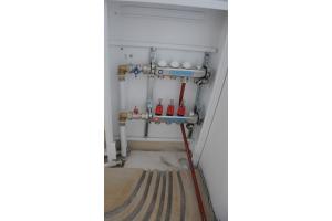 Verteileranschluss einer Fußbodenheizung in einem Verteilerkasten.