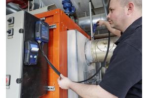 Kundendienstmonteur Christian Michel von der Profi-Wärme-Service GmbH misst die Abgas-Emissionen an einem Brenner.
