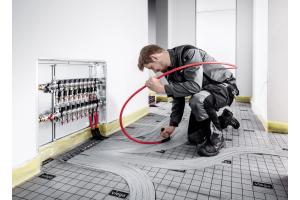 """Ein Installateur beim Einbau einer """"Fonterra""""-Fußbodenheizung."""