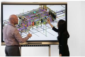 Zwei Planer besprechen ein BIM-Modell auf einem Bildschirm.
