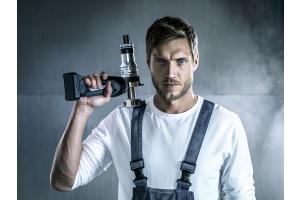 """Ein Handwerker und das Akku-Werkzeug """"Rautool A-one"""" von Rehau."""