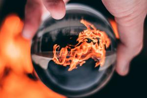 Eine Hand hält eine Glaskugel, in der sich ein Feuer spiegelt.