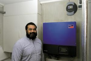 Ein Mann steht vor einem Photovoltaik-Anlagen-Überwachungssystem.