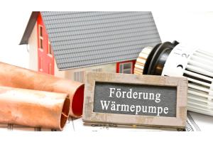 "Kreidetafel mit den Wörtern ""Förderung Wärmepumpe""."