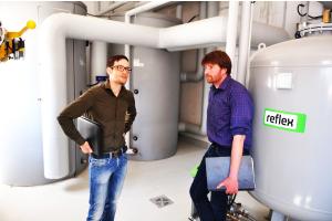 Zwei Männer stehen in einem Heiztechnikraum vor zwei Pufferspeichern.