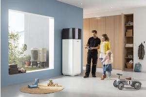 """Eine Wärmepumpen """"ROTEX HPSU compact Ultra"""" in einem Wohnzimmer, eine Frau und ein Monteur stehen davor."""