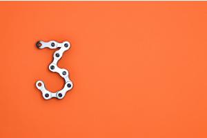 Eine Drei aus einer Metallkette vor einem orangen Hintergrund.