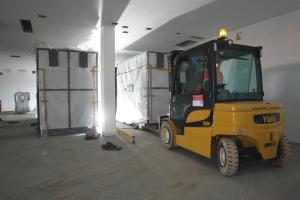 Ein Gabelstapler bringt eine Großwärmepumpe in einen Technikraum ein.