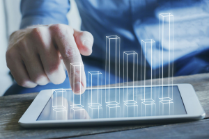 Ein Mann bedient ein Tablet, aus dem verschiedene digitale Säulen hervorwachsen.