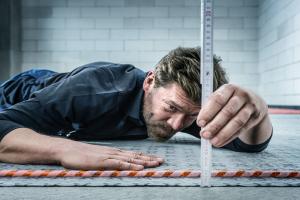 """Ein Handwerker misst die Höhe des Fußbodenheizungs-Klettsystem """"Rautherm Speed""""."""